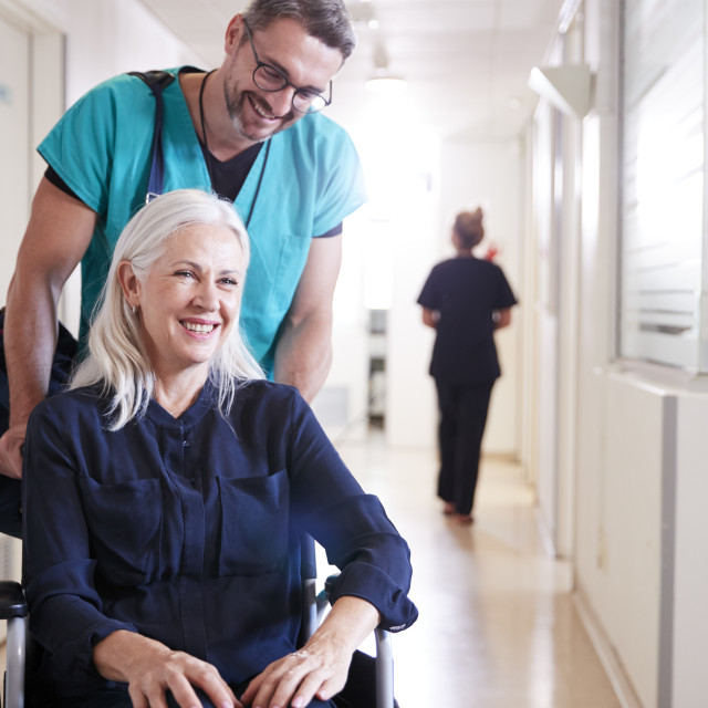 """""""Male Orderly Pushing Senior Female Patient Being Discharged From Hospital In..."""" stock image"""