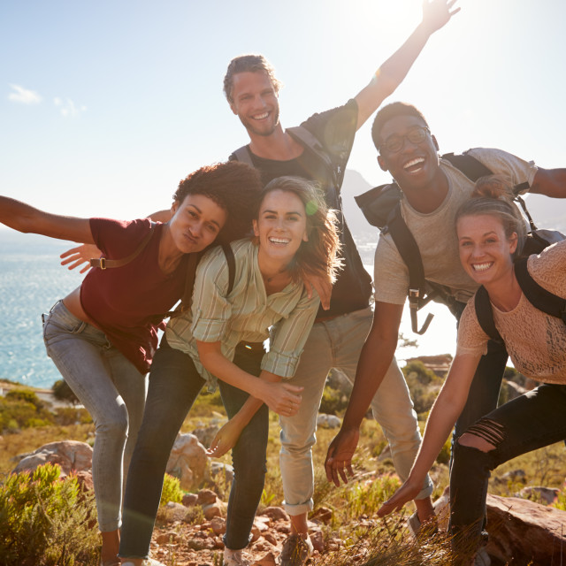 """Millennial friends on a hiking trip reach the summit and have fun posing for..."" stock image"