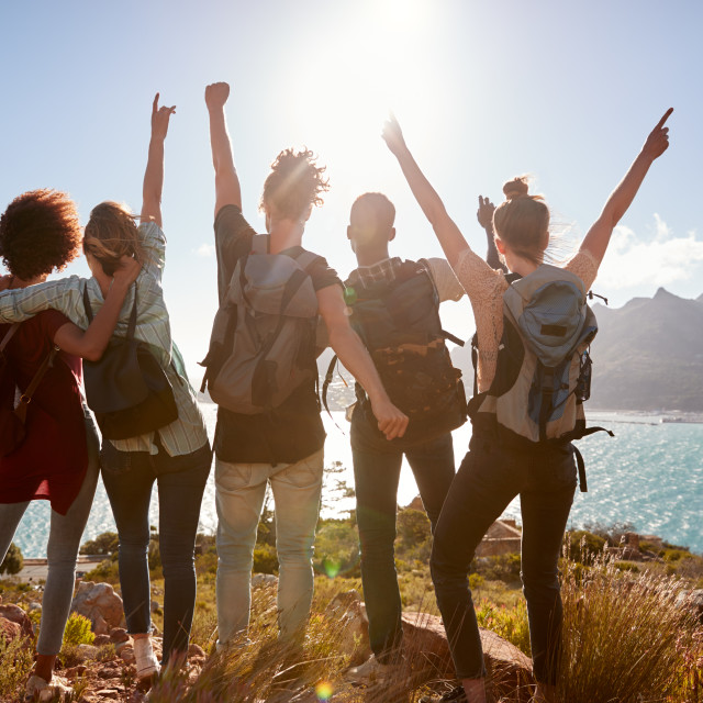 """Millennial friends on a hiking trip celebrate reaching the summit and admire..."" stock image"