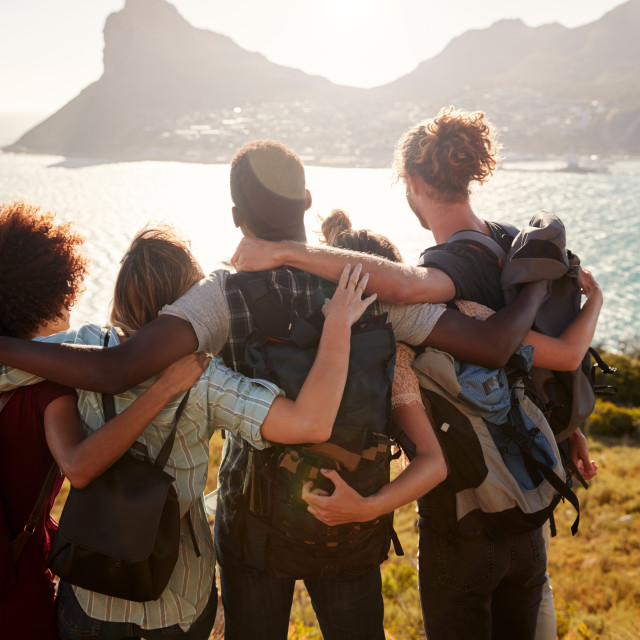 """Millennial friends on a hiking trip reach the summit and embrace, admiring..."" stock image"