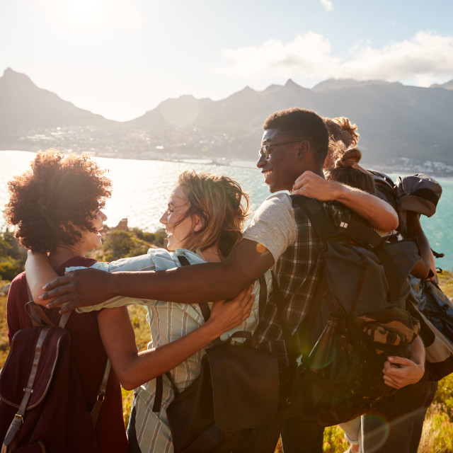 """Millennial friends on a hiking trip embrace at the summit to celebrate their..."" stock image"