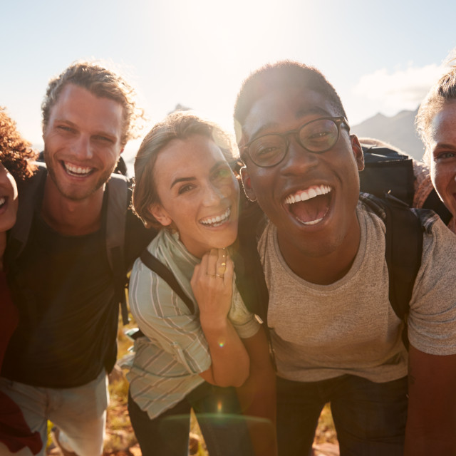 """Young adult friends on a hike celebrate reaching the summit, smiling to..."" stock image"
