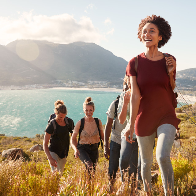"""Millennial African American woman leading friends on an uphill hike by the..."" stock image"