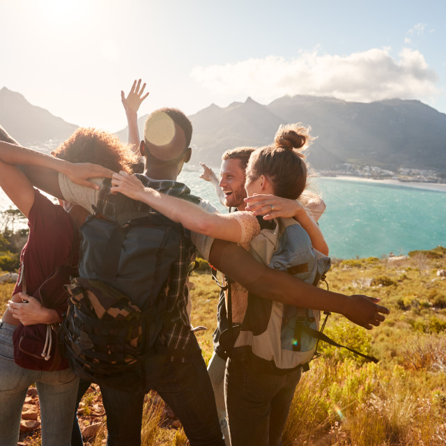 """Young adult friends on a hike celebrate reaching a summit near the coast..."" stock image"