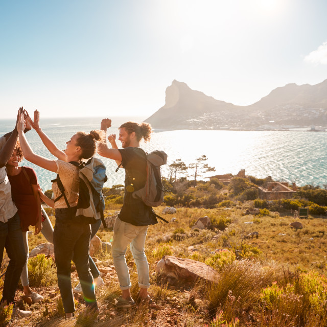 """Young adult friends on a hike celebrate reaching a summit near the coast,..."" stock image"