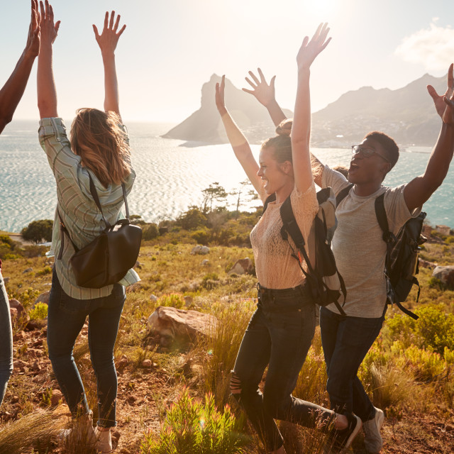 """Millennial friends on a hiking trip celebrate reaching the summit, cheering..."" stock image"