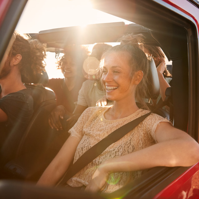 """Happy millennial friends on a road trip vacation driving in an open car,..."" stock image"