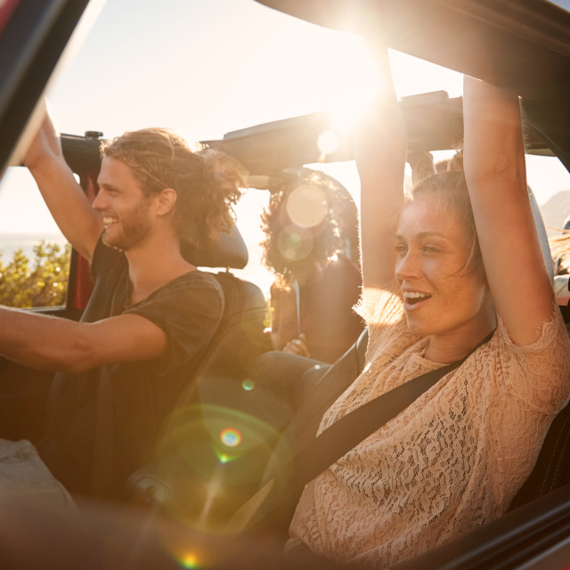 """Excited millennial friends on a road trip vacation driving in an open car,..."" stock image"