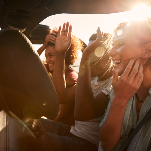"""Happy young adult friends on a road trip vacation travelling in the back of..."" stock image"