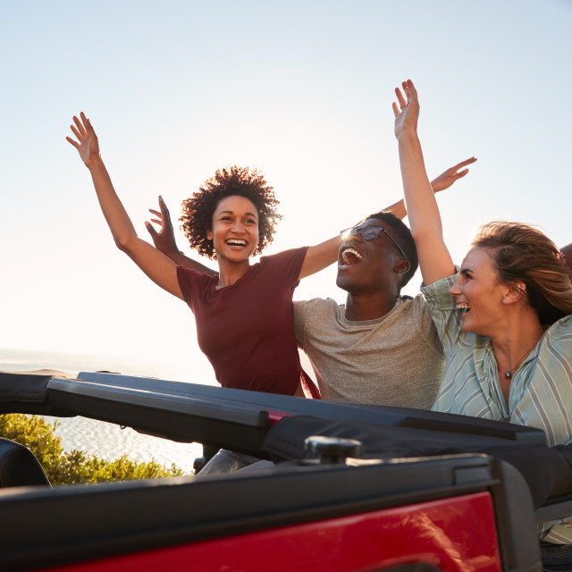 """Excited millennial friends travelling in the back of an open car with their..."" stock image"