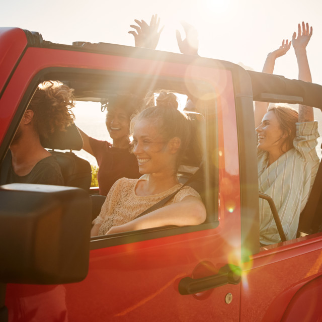 """Excited young adult friends on a road trip vacation driving in an open top..."" stock image"