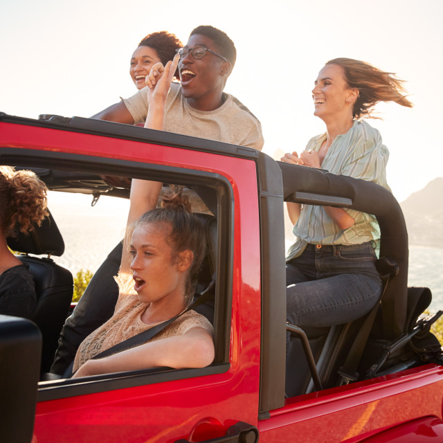 """Five young adult friends on a road trip driving in an open top jeep by the sea"" stock image"
