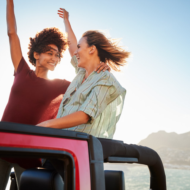 """Two millennial female friends on a road trip standing in the back of an open..."" stock image"