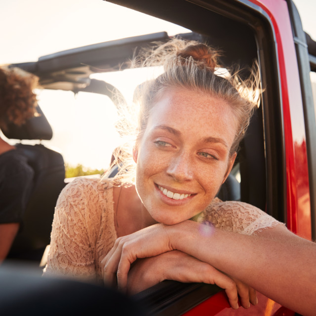 """Millennial white couple on a road trip driving in open top car, women leaning..."" stock image"