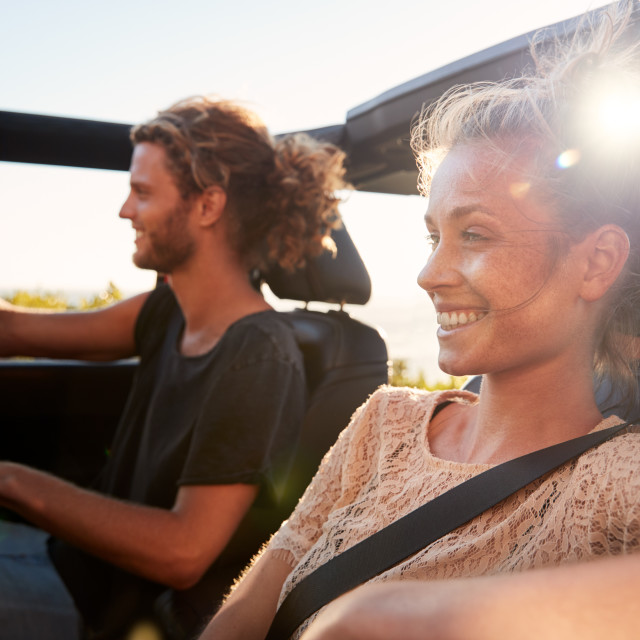 """Millennial white couple on a road trip driving in an open top car, backlit,..."" stock image"