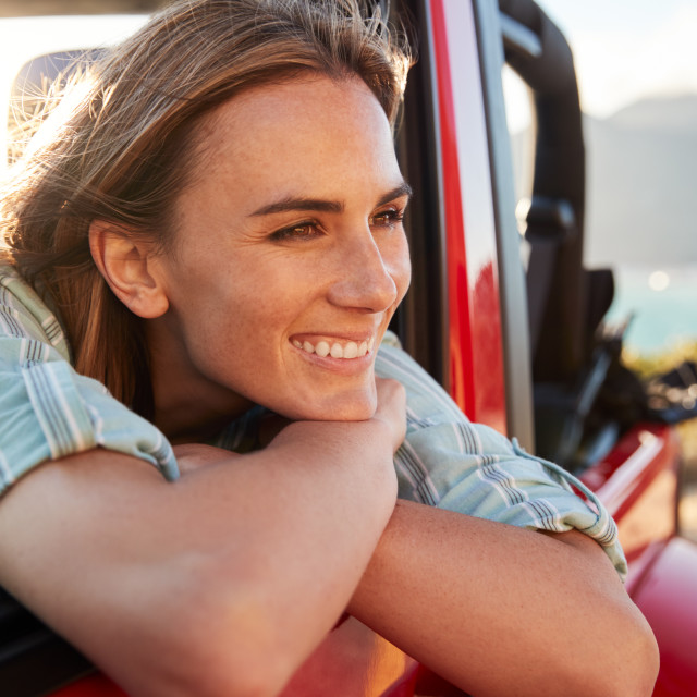 """Millennial white woman on a road trip with friends leaning on car door..."" stock image"