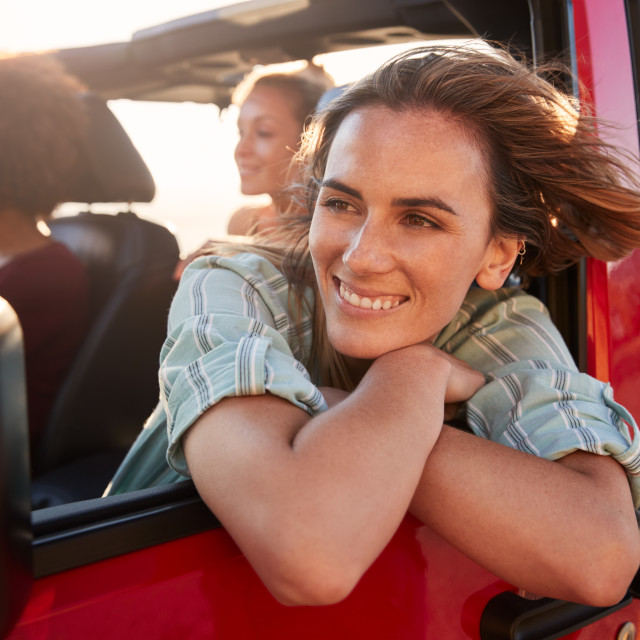 """Millennial white woman on a road trip with friends, leaning looking out of..."" stock image"