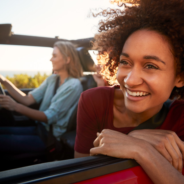 """Millennial African American woman on a road trip with friends, leaning out of..."" stock image"