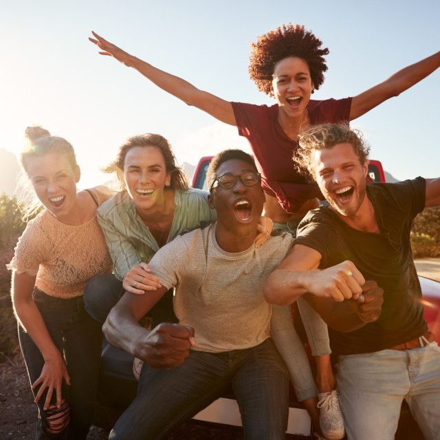"""Five millennial friends on a road trip have fun posing for photos at the..."" stock image"