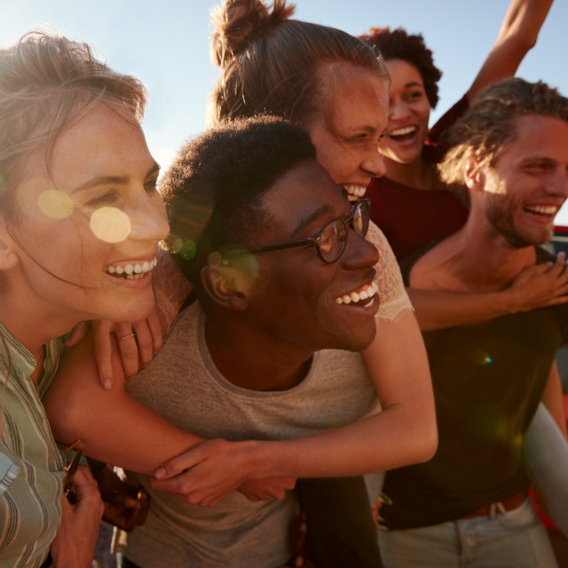 """Five millennial friends on a road trip have fun piggybacking at the roadside,..."" stock image"