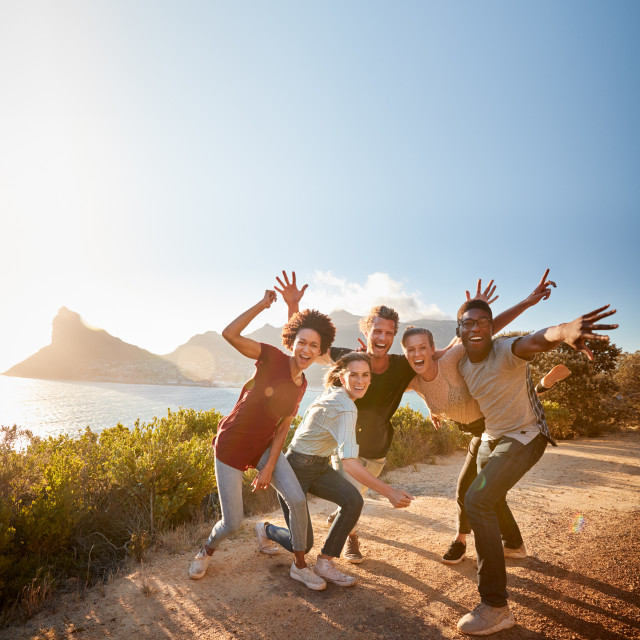 """Five millennial friends on a road trip have fun posing for photos on a..."" stock image"