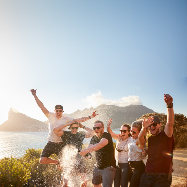 """Six young adult friends celebrating on a coastal path opening a bottle of..."" stock image"