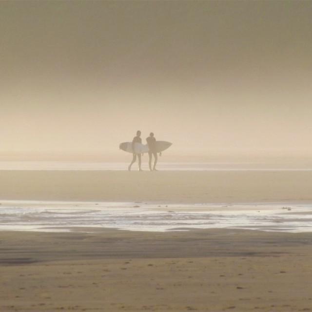 """Surfers on Pembrokeshire beach"" stock image"