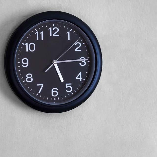 """""""Black round wall watch is show quarter past five o'clock."""" stock image"""