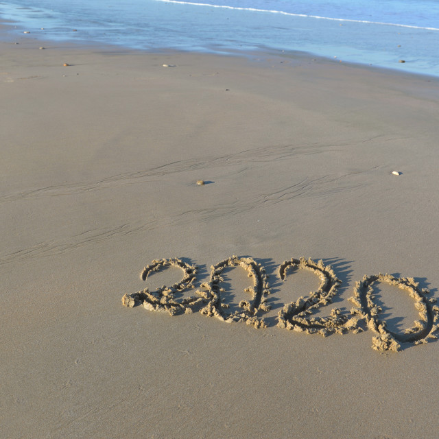 """2020 written on the sand to the beach"" stock image"