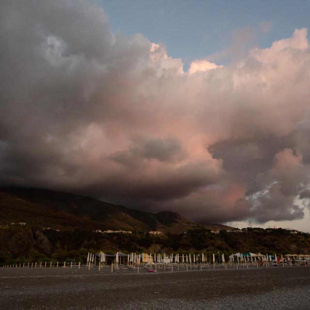 """Dramatic sky over a beach as the sun is setting, Praia a Mare, Italy"" stock image"