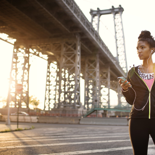 """""""Woman listening to music through headphones while standing on city street"""" stock image"""