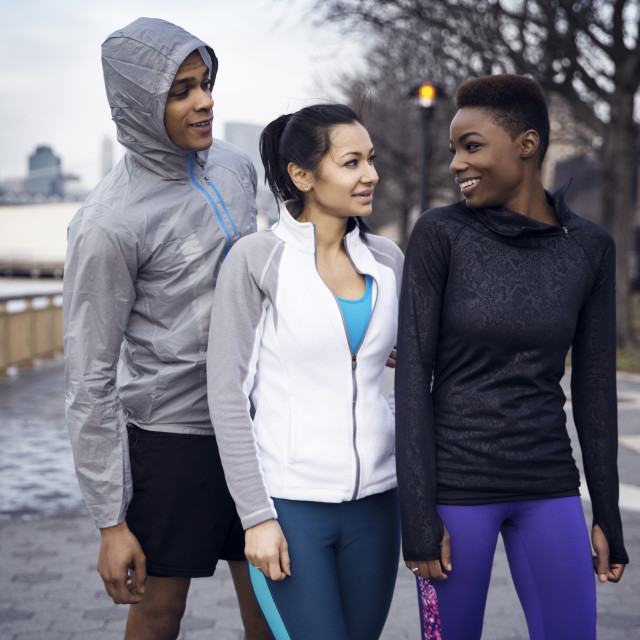 """Happy multi-ethnic athletes talking on footpath"" stock image"