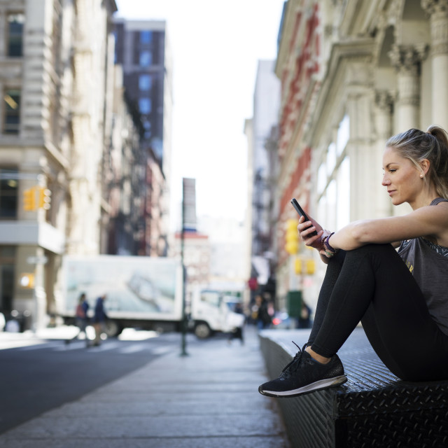 """""""Female athlete using mobile phone while sitting at sidewalk in city"""" stock image"""