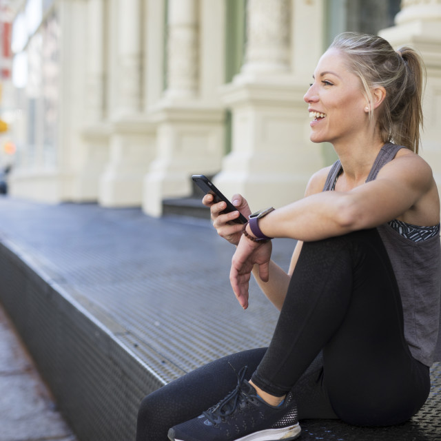 """""""Happy athlete using mobile phone while sitting at sidewalk in city"""" stock image"""