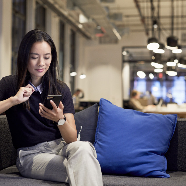 """""""Confident entrepreneur using mobile phone while sitting on sofa at creative..."""" stock image"""