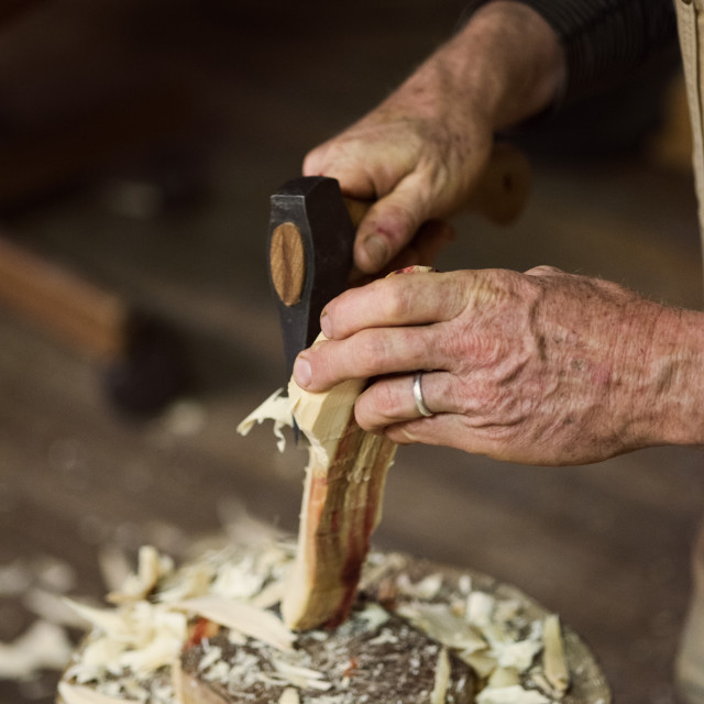 """Cropped imager of carpenter shaping wood with chisel hammer at workshop"" stock image"