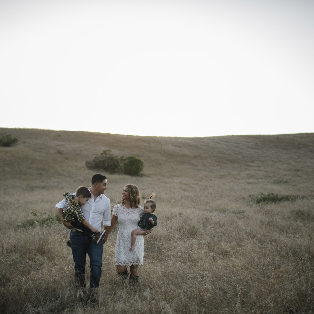 """""""Happy family walking on field against cleat sky"""" stock image"""