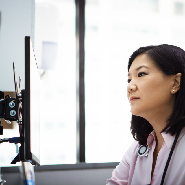 """""""Female doctor using desktop computer in clinic"""" stock image"""