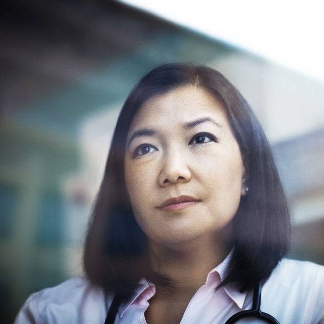 """""""Thoughtful female doctor looking through window"""" stock image"""