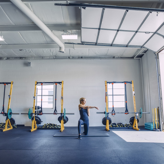 """Woman stretching arms while kneeling against barbells in gym"" stock image"