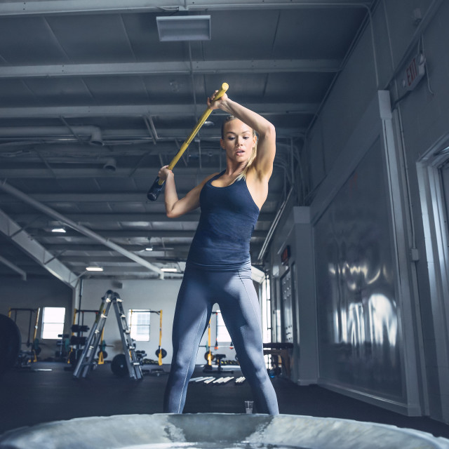 """""""Woman hitting tire with sledgehammer while training at gym"""" stock image"""