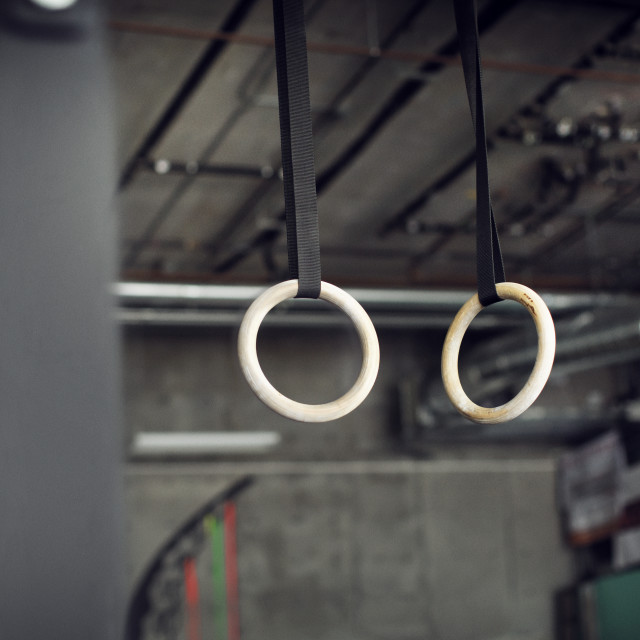 """""""Low angle view of gymnastic rings hanging in gym"""" stock image"""