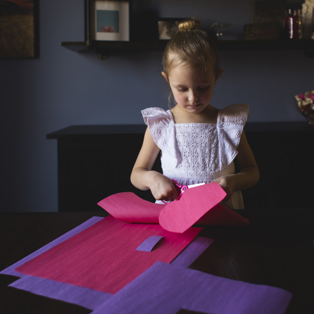 """""""Girl cutting craft papers on table at home"""" stock image"""