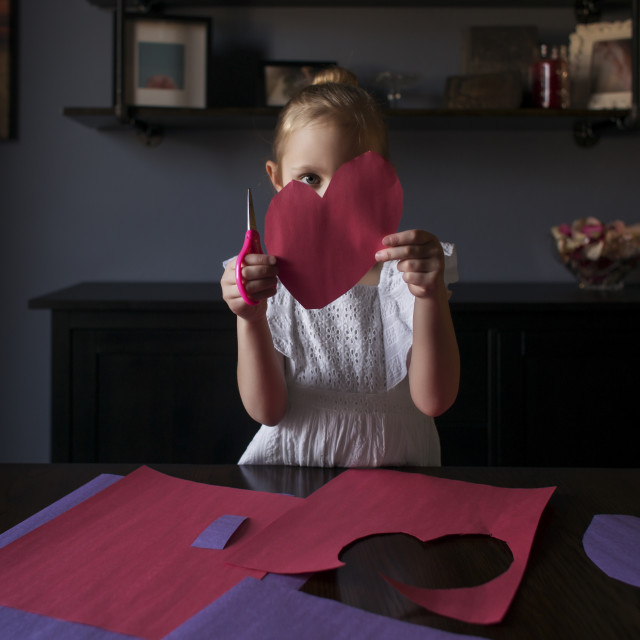 """""""Girl cutting craft papers in heart shape on table at home"""" stock image"""
