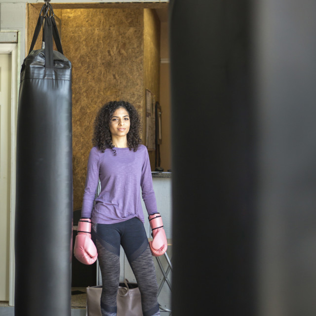 """""""Portrait of female boxer standing by punching bag in gym"""" stock image"""