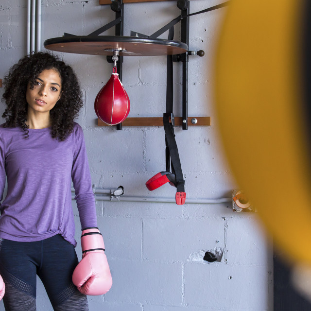 """""""Portrait of female boxer standing by wall in gym"""" stock image"""
