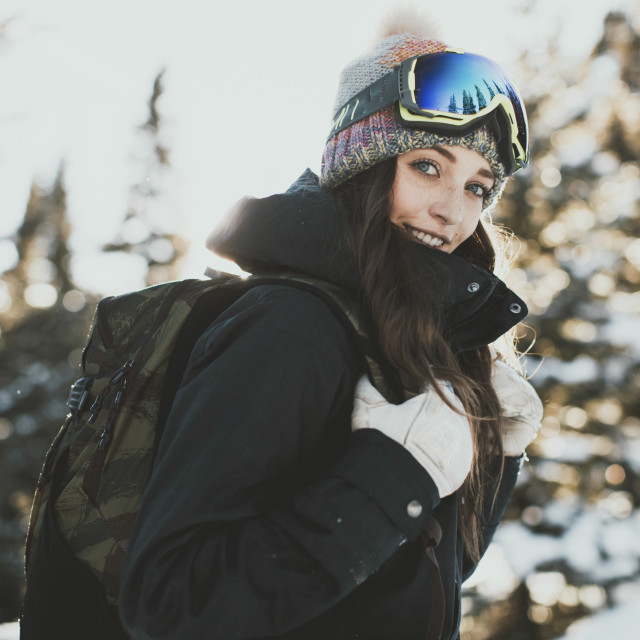 """""""Portrait of confident young woman with backpack wearing ski goggles during..."""" stock image"""
