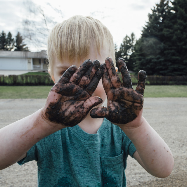 """Boy with dirty hands standing on road"" stock image"