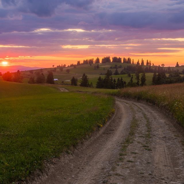 """sunset over a mountain road leading through meadows"" stock image"