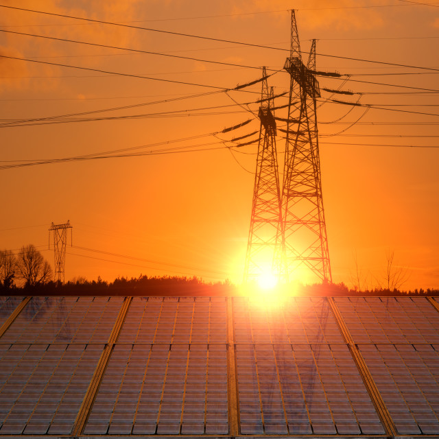"""Solar panels with electricity pylon at sunset. Clean energy concept"" stock image"